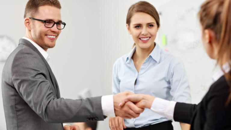 Darbinieks mēģina iejusties jaunā darba kolektīvā - rokasspiediens starp sievieti un vīrieti, fonā redzama trešā darbiniece