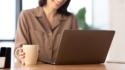 Sieviete sēž pie portatīvā datora ar krūzi un domā, kā uzrakstīt motivācijas vēstuli.